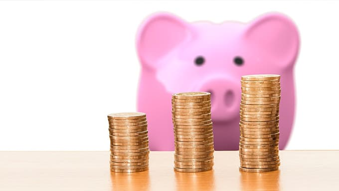 Un tirelire cochon regarde trois colonnes de pièces jaunes posées sur une table