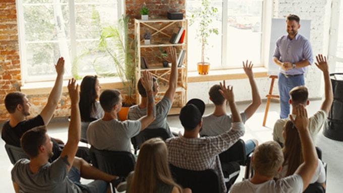 Un formateur en fond est face à ses apprenants qui lèvent les bras