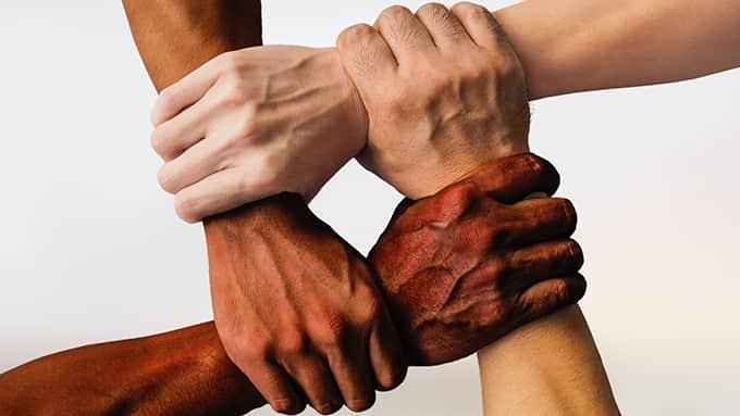 4 mains de couleur de peau différentes se tiennent conjointement le poignet.