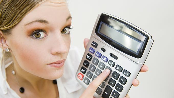Une femme blonde tient à la main gauche une calculatrice.