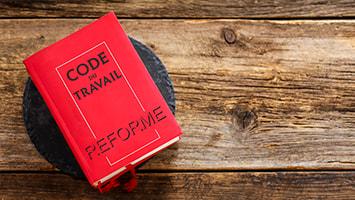 """Mot """"Réforme"""" sur une édition du code du travail posé sur une table en bois"""