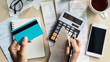 les mains d'une personne comptabilisent des notes de frais